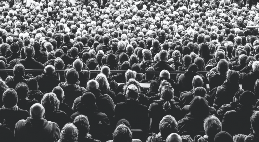 The Image shows an audience in black and white.