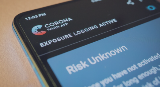 The image shows a picture of a smartphone with the Corona Warn App.