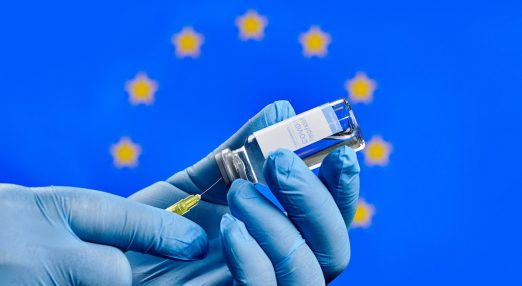 EU flag in the background, with a COVI-19 vaccine in the foreground.