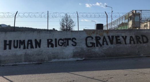 """Human rights graveyeard"" sign on a border wall"